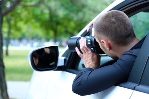 Detective privado haciendo una foto oculto en un coche
