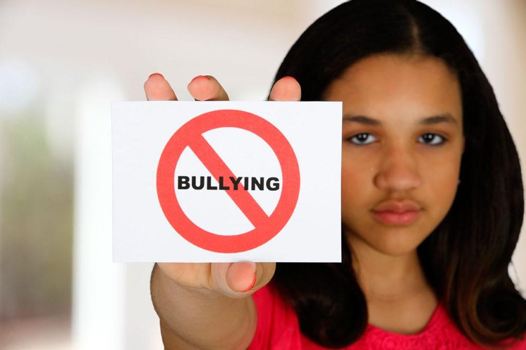 niña con letrero de stop acoso escolar